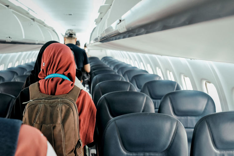 Rear view of people standing in airplane