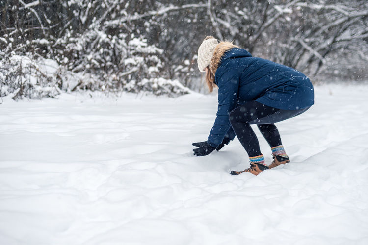 Side view of woman on snow field
