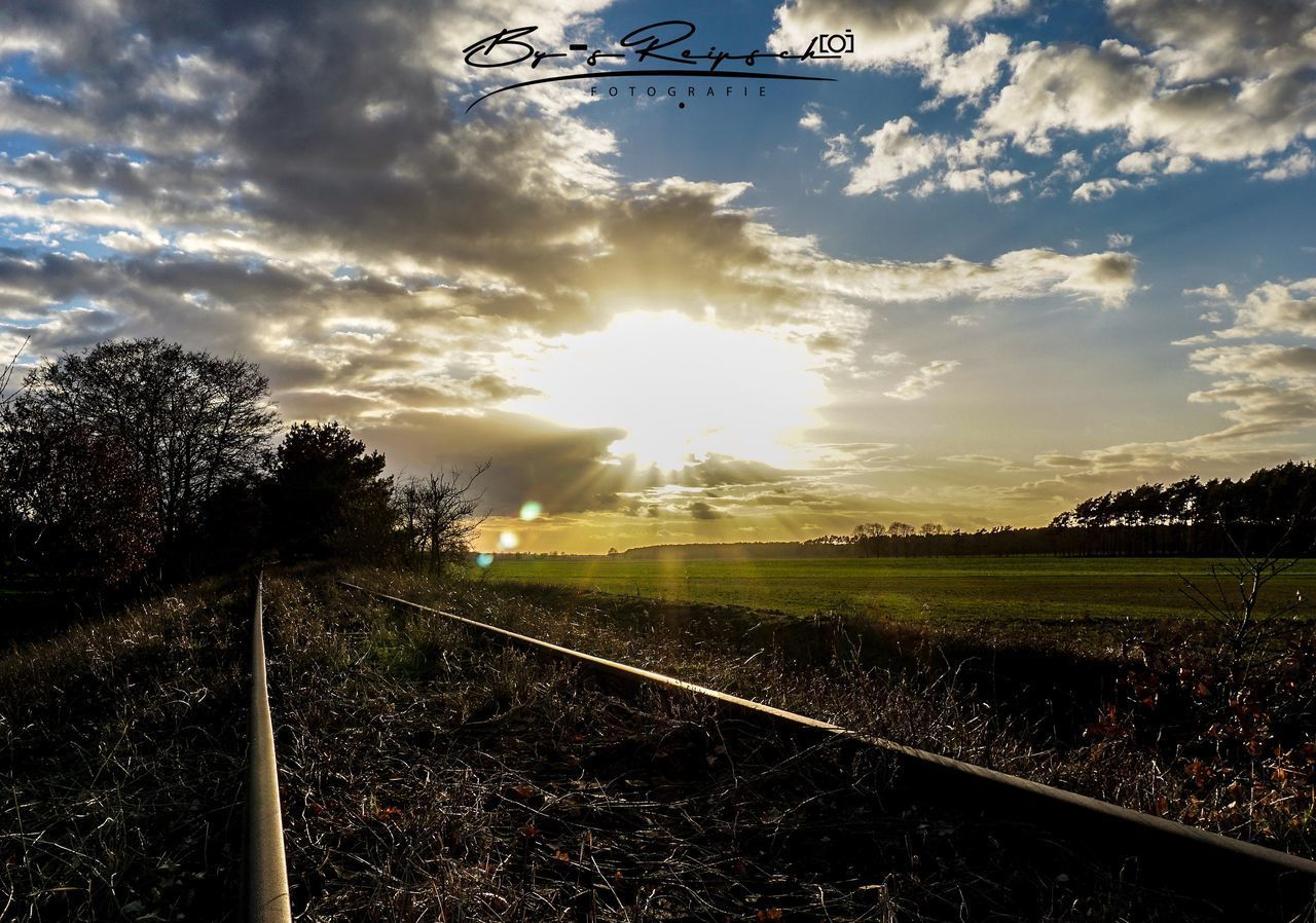 RAILROAD TRACK AMIDST FIELD AGAINST SKY AT SUNSET