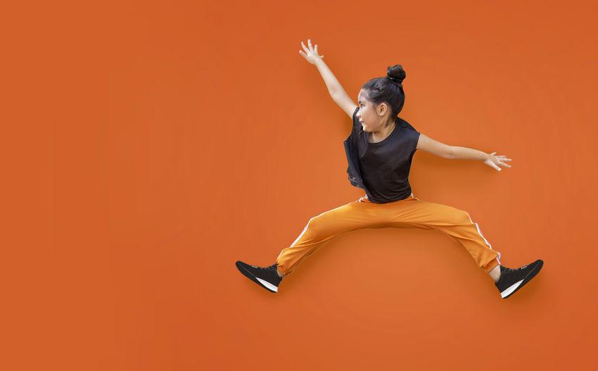 Full length of man jumping against orange background