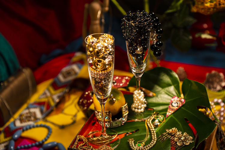 Celebrational Abundance Abundance Wealth Celebration Decoration Jewelry Pearls Focus On Foreground Indoors  Glass Table Gold Colored No People Art And Craft Close-up Refreshment High Angle View Food And Drink Drink Drinking Glass Still Life Alcohol Luxury Sculpture Household Equipment