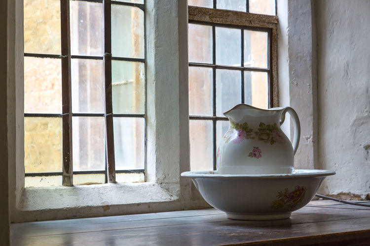 An old fashioned jug sat in a washing bowl on a window ledge at Chastleton House Window Indoors  Day No People Glass - Material Window Sill Transparent Container Table Bowl Nature Still Life Domestic Room Wall - Building Feature Architecture Ceramics Design Floral Pattern Washing Jug Wash Bowl Chastleton House National Trust Windowsill Heritage Building Heritage