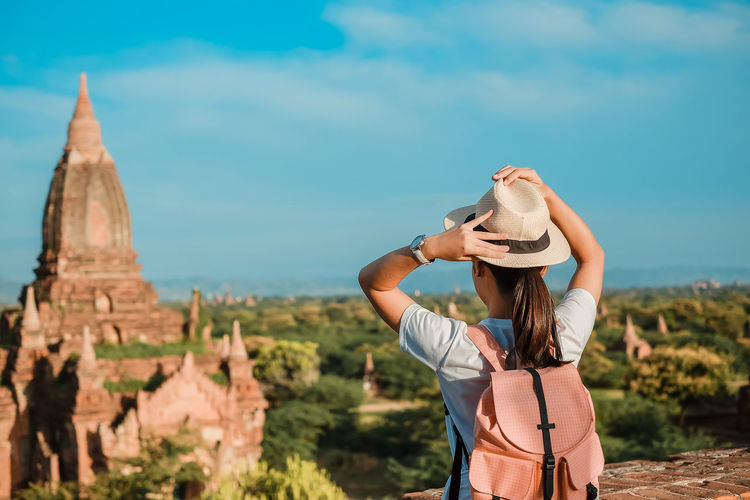 Young woman traveling backpacker with hat, Asian traveler standing on Pagoda and looking Beautiful ancient temples, landmark and popular for tourist attractions in Bagan, Myanmar. Asia Travel concept Hat One Person Lifestyles Sky Real People Leisure Activity Standing Nature Clothing Tourism Young Adult Young Women Focus On Foreground Travel Destinations Travel Architecture Day Women Casual Clothing Hair Hairstyle Sun Hat Outdoors Bagan Myanmar