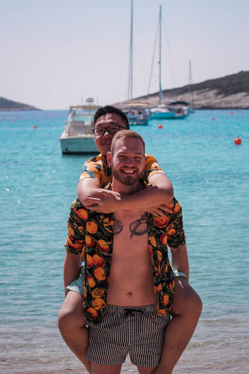 Portrait of happy homosexual couple at beach against clear sky