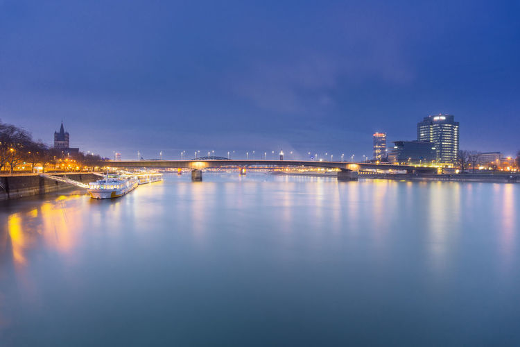 View of the beautiful long River Rhine, Ships and the illuminated Skyline of Cologne in the Evening - in Germany Cologne 2018. Blue Sky Evening Night River Rhine Deutzer Bridge No People Illuminated City Reflection Building Exterior Architecture Sky Water Cologne Ships Skyline Germany Long Exposure Built Structure Building Dusk Travel Destinations Connection Waterfront Bridge Nature Cityscape Outdoors Skyscraper