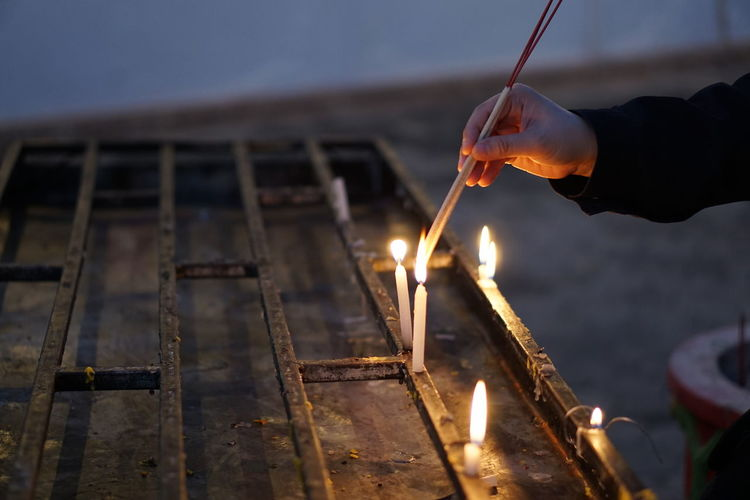 Cropped hand of person burning incense sticks with candle