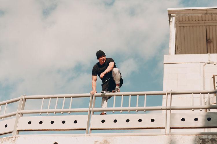 Men standing on railing against sky