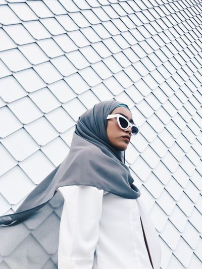 Woman wearing sunglasses and hijab while standing against wall