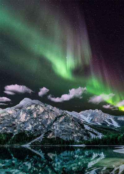 Scenic view of lake and mountains against aurora borealis at night