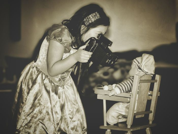 Side view of girl photographing doll on chair at home