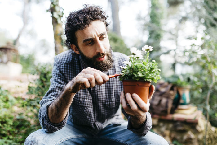 YOUNG MAN SITTING IN POT