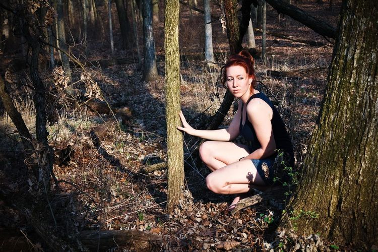 Young woman crouching against trees at forest