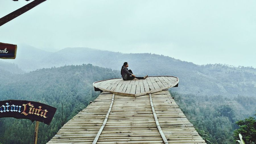 Side view of woman sitting on wood against sky
