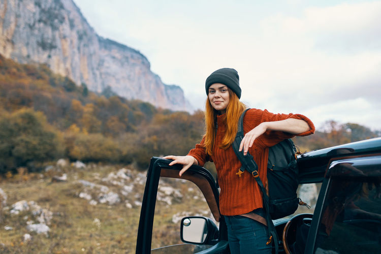 Young woman smiling while standing on car