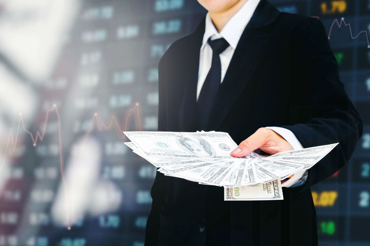 Midsection of businessman holding paper currency against share market data