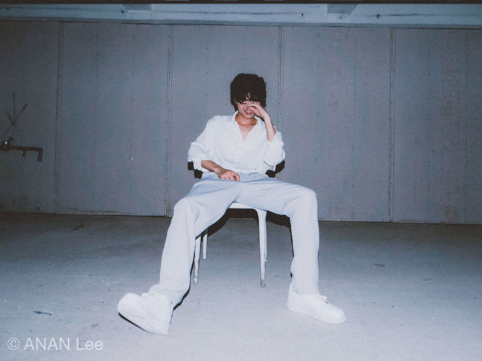 Full length of young man sitting on chair against wall