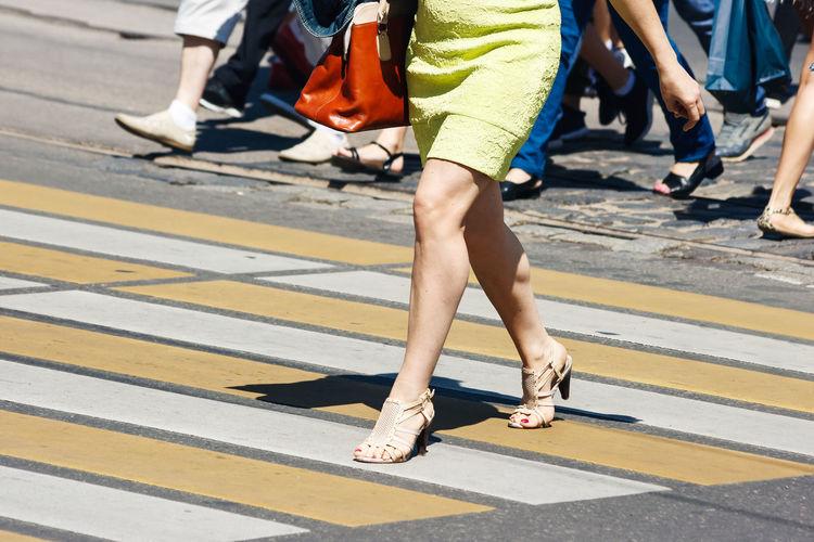 Low section of people walking on zebra crossing in city