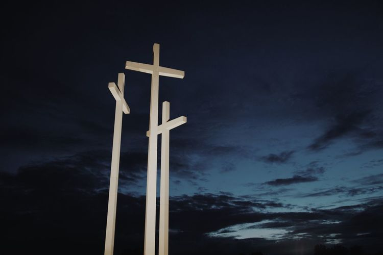 Low angle view of crosses against sky at night