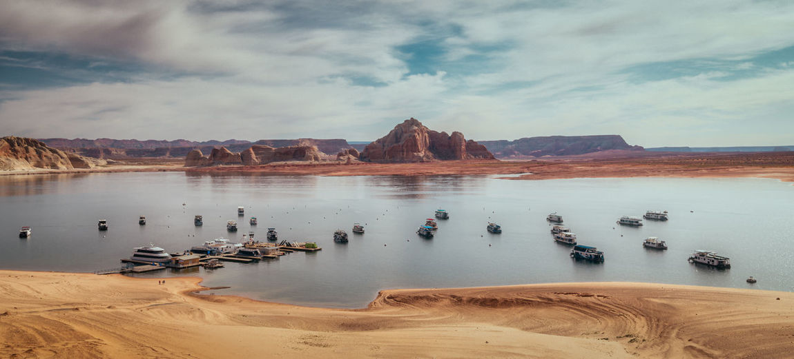 Panorama of boats on lake powell, arizona with low water level.