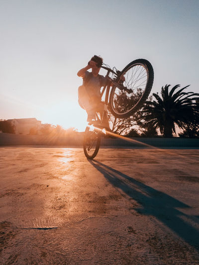 Low angle view of man performing stunt on bicycle on footpath