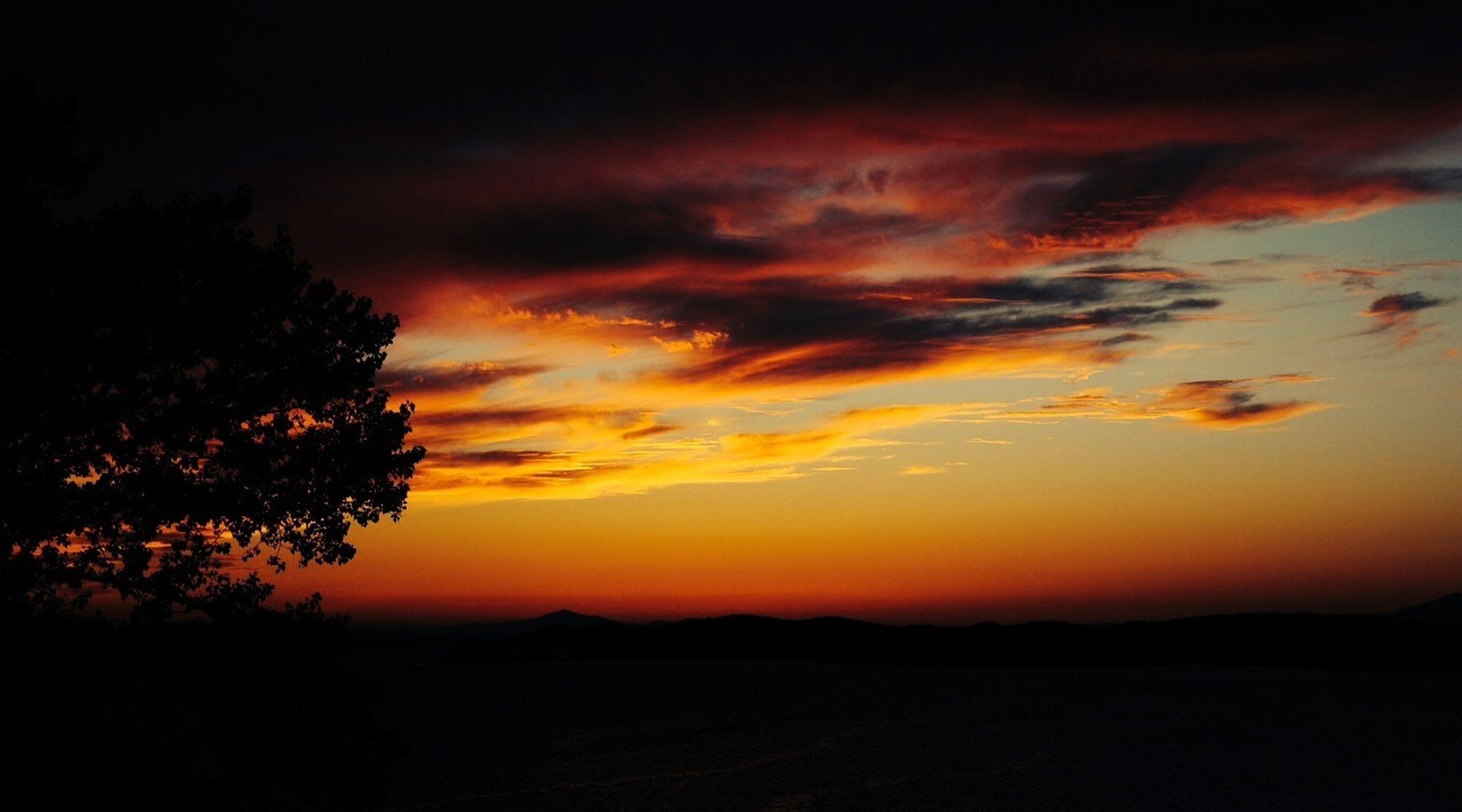 sunset, silhouette, scenics, tranquil scene, beauty in nature, tranquility, orange color, sky, dramatic sky, idyllic, nature, landscape, cloud - sky, majestic, tree, dark, cloud, awe, atmospheric mood, moody sky