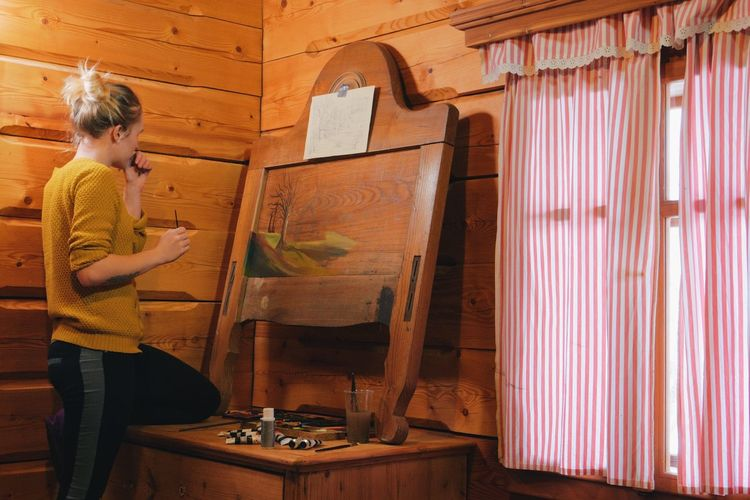 Woman drawing on canvas while standing in cottage
