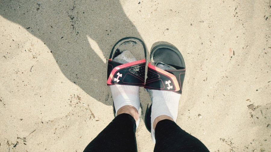 Too Big Sandals Feet Low Section Real People One Person Shoe Human Leg High Angle View Day Leisure Activity Human Body Part Standing Lifestyles Outdoors Sand Beach Sunlight Adults Only Woman Legs