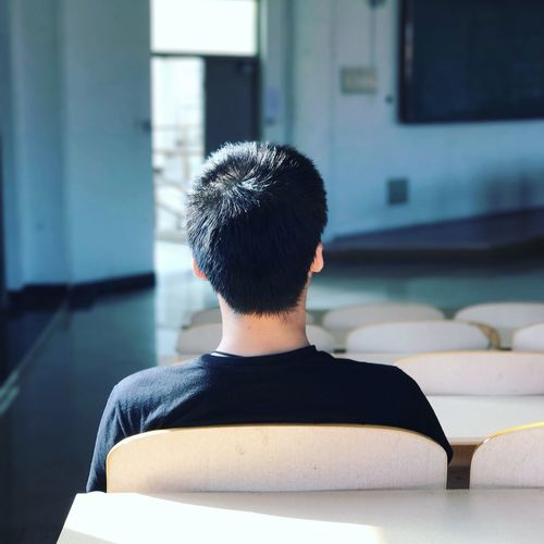 Rear View Of Man Sitting In Classroom