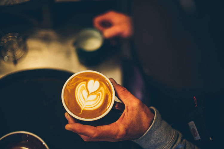 Cropped hand of person holding cappuccino