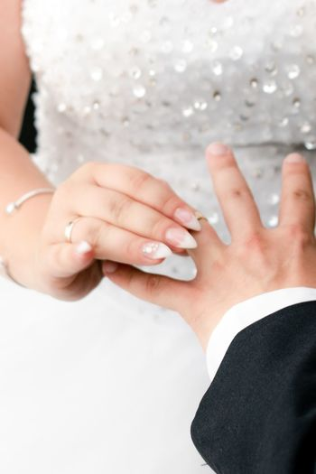 Midsection Of Bride Putting Ring On Finger