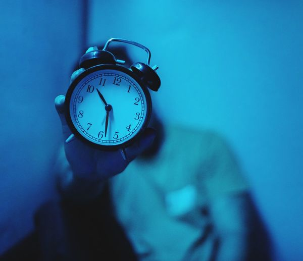Man holding alarm clock while sitting against wall at home