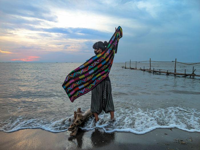 Woman with umbrella on beach against sky