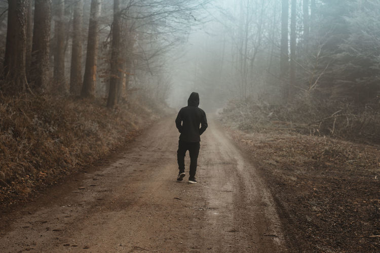 back of single boy walking through a foggy forest landscape in a country footpath Direction Fog The Way Forward Land Walking Thinking Forest Forestwalk Foggy Melancholy Outdoors Footpath Nature WoodLand Dirt Road Alone Lonely Leisure Activity Lifestyles