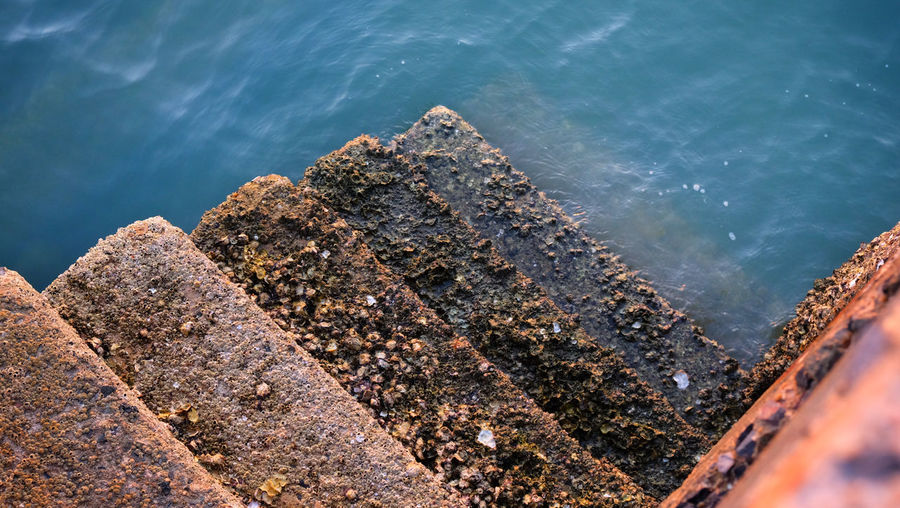 Concrete stairway old fishing port's with barnacle reef and sea water background.
