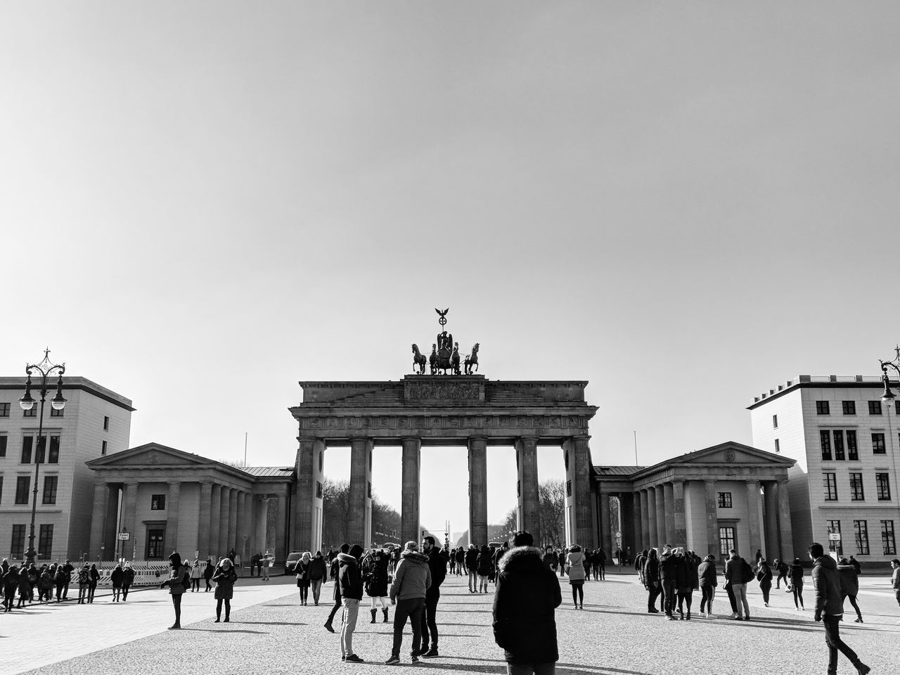large group of people, travel destinations, statue, architecture, built structure, tourism, building exterior, art and craft, sculpture, travel, real people, history, city gate, vacations, women, clear sky, monument, outdoors, day, low angle view, architectural column, men, sky, city, people, adult, adults only