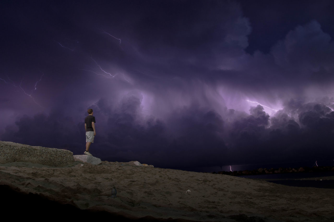 Full length of man standing on mountain against sky at night