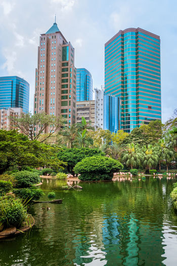 Lake and buildings against sky in city