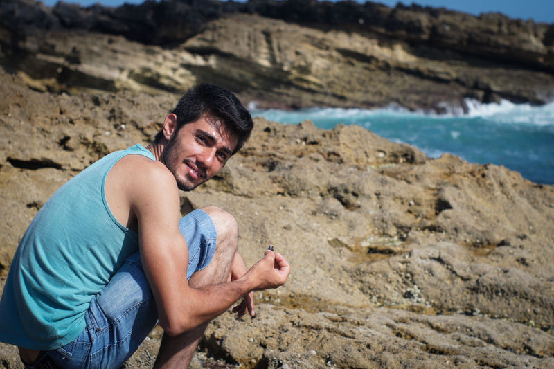 Portrait of smiling man crouching on shore at beach