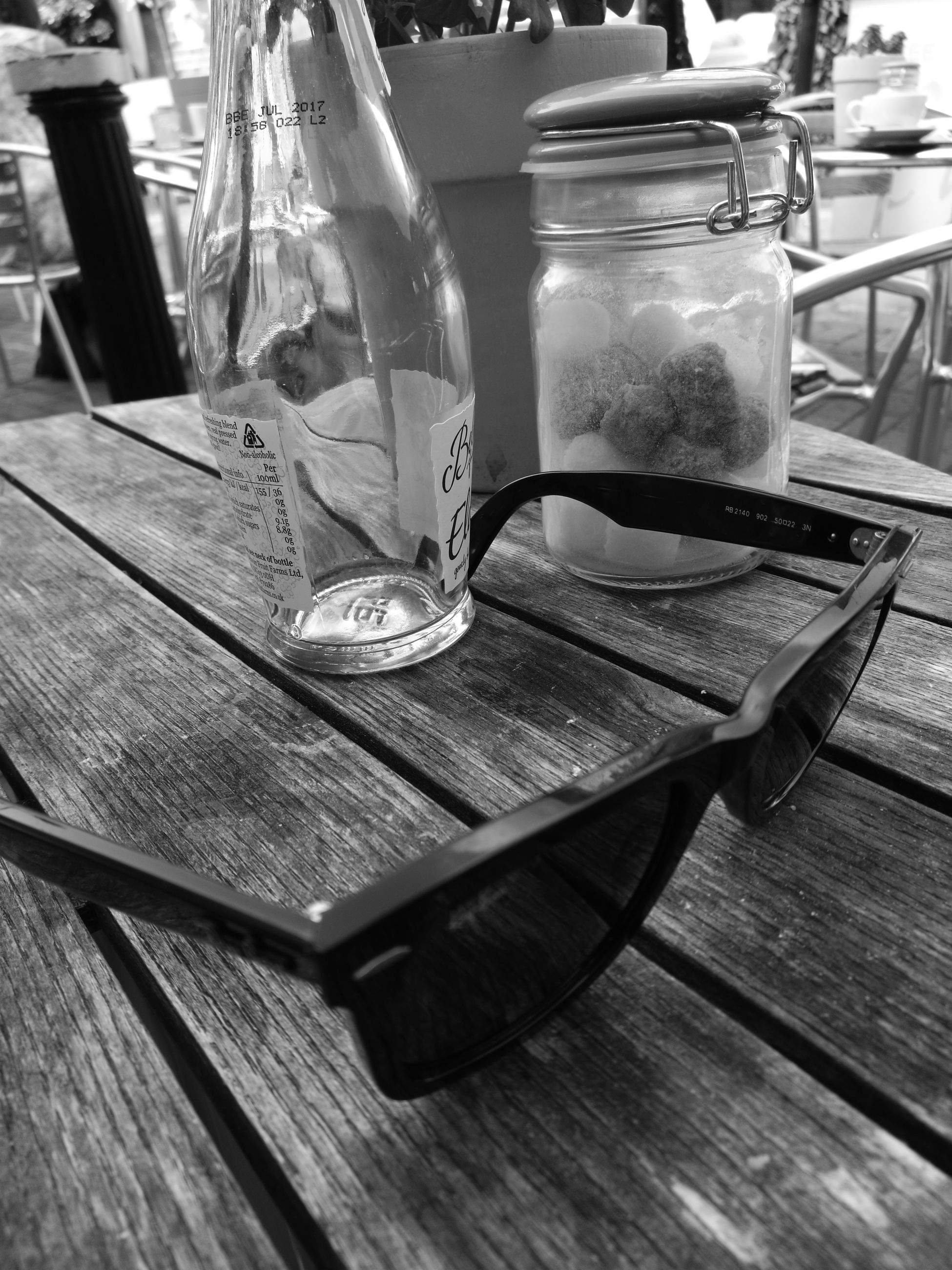 table, indoors, chair, empty, restaurant, absence, still life, drinking glass, drink, wood - material, glass - material, sidewalk cafe, cafe, place setting, furniture, no people, seat, refreshment, day, food and drink
