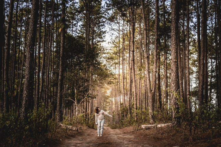 Woman standing on dirt road amidst trees in forest