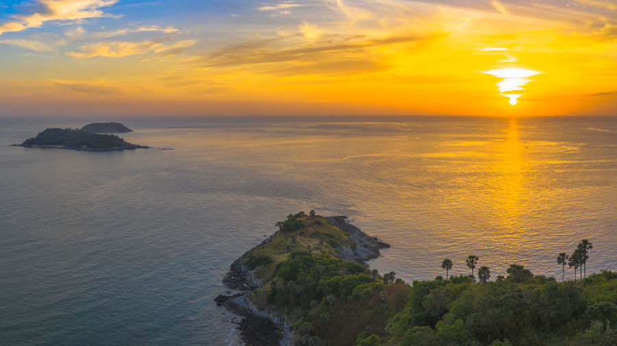 aerial photography sunset at Laem Promthep Cape viewpoint. Promthep cape is the most popular viewpoint in Phuket. the most tourist always come to see sunset at this landmark Phuket,Thailand Promthep, Cape, Dracula, Venice Sugar Palm, Sky Sunset Cloud - Sky Scenics - Nature Beauty In Nature Nature Water Horizon Over Water Travel Tourism Destination Popular, Thanks! Sea Rock Horizon Tranquil Scene Solid Tranquility Rock - Object Land Orange Color Beach Idyllic Sun Outdoors