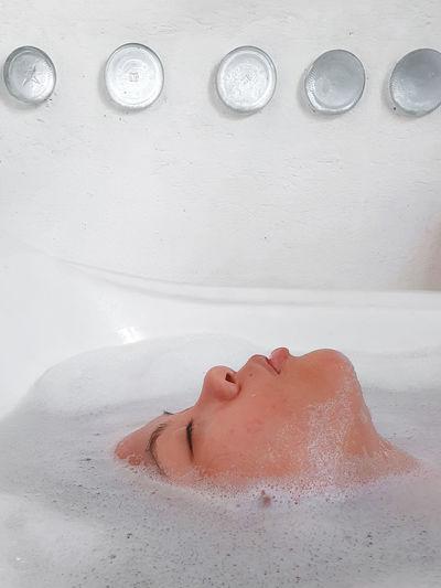 Profile of a woman lying down in bathtub
