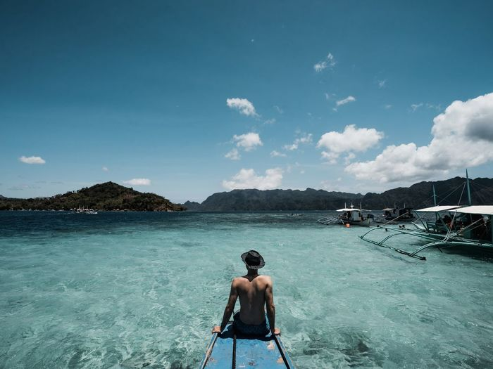 Rear view of shirtless man on sea against sky