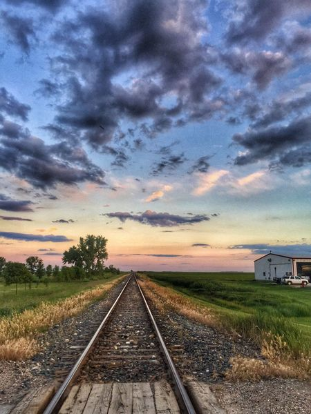 Railroad Track Rail Transportation Transportation Cloud - Sky Sky Sunset The Way Forward No People Built Structure Nature Grass Public Transportation Landscape Scenics Outdoors Architecture Beauty In Nature Building Exterior Day Tree