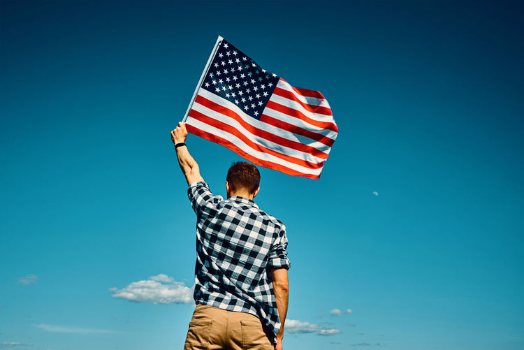 American flag outdoors. man holds usa national flag against blue cloudy sky. 4th july