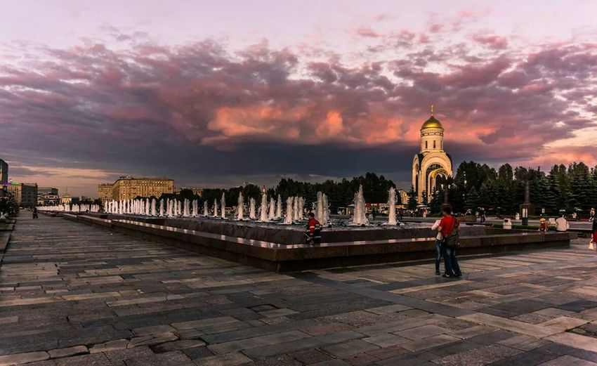 Tourists In Park Near Kazan Cathedral Against Cloudy Sky