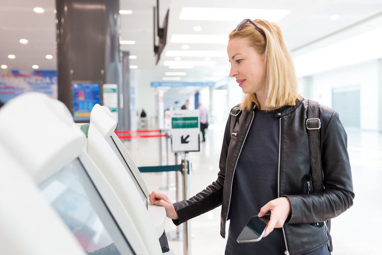 Mid adult woman using atm machine at airport