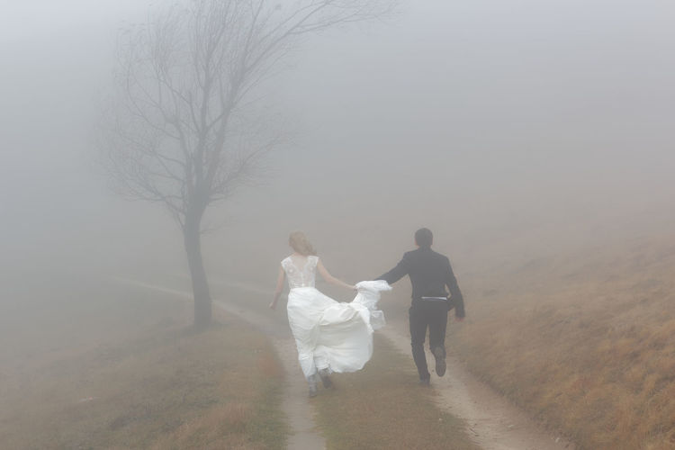 Rear View Of Newlywed Couple Running On Field During Foggy Weather
