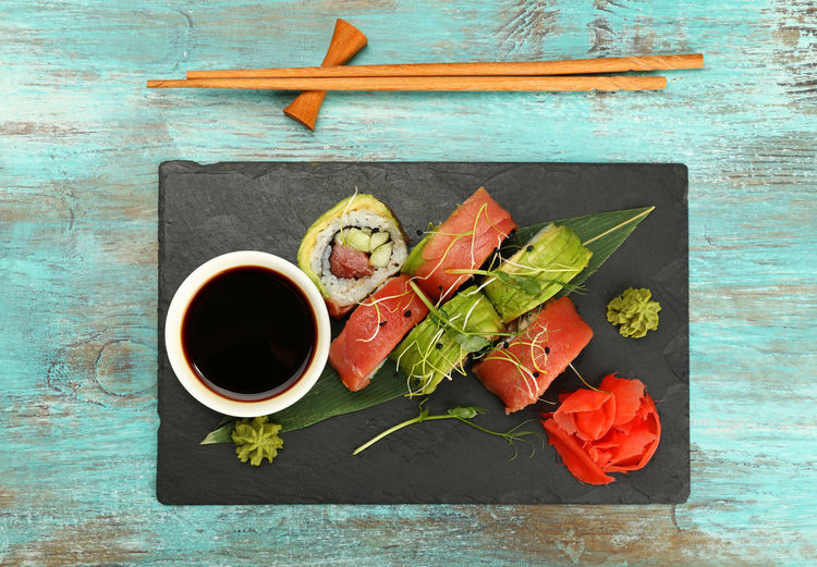 Portion of tuna and avocado sushi rollson slate board on table Set Chopsticks Japanese Food Soy Sauce Seafood Ready-to-eat Food And Drink Food Directly Above Freshness Healthy Eating Wood - Material Table No People Vegetable High Angle View Sauce Asian Food Wellbeing Bowl Tuna Tunafish Avocado Mix Sushi Sushi Rolls Restaurant Gourmet Cuisine Raw Food Ginger Wasabi Culinary Serving Size