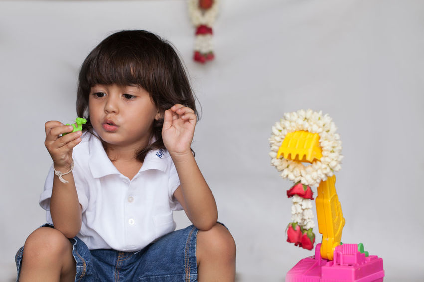 a long hair boy in white shirt and jean playing toy on the ground while waiting for his mom in Mother Day Long Hair, Don't Care. People, Smile, Bangs Boy,  Casual Clothing Child Childhood Females Flower Front View Garland, Girls Hairstyle Holding Indoors  Innocence One Person Plant Play, Kids, Family, Fun, Smile Portrait Sitting Sweet Sweet Food Toy, Women